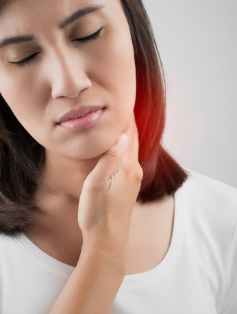 Woman holding her neck near thyroid